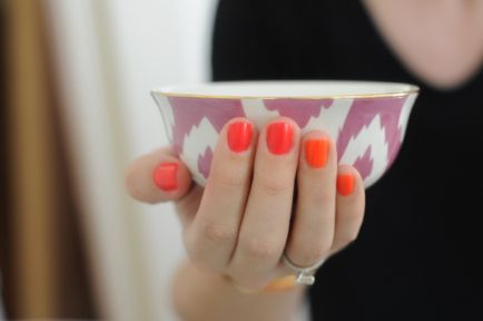 Eyeing Cupcakes and Cashmere's bright orange manicure.