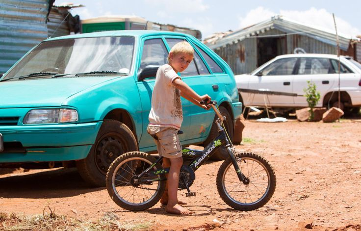 Pictured: A child playing in the camp. These white South African families are so poor they are forced to live in slums similar to the worst days of Apartheid. At this 'white squatter camp', hundreds of families have no power, barely any food or water and must live in poor shelter. Townships like this, which can be found all across the country, are a direct result of white poverty following Apartheid - which came to an end 22 years ago. Under the old white supremacist regime, which ended in…