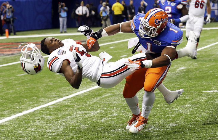 Florida linebacker Jon Bostic (1) hits Louisville quarterback Teddy Bridgewater (5) hard enough to dislodge his helmet in the first quarter of the Sugar Bowl NCAA college football game Wednesday, Jan. 2, 2013, in New Orleans.