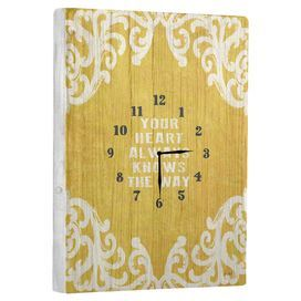 """Wood wall clock with a typographic face and scrolling details.   Product: Wall clockConstruction Material: Wood Color: Yellow Features: Arrives ready to hangTypographic faceScrolling detailsAccommodates: Batteries - not includedDimensions: 20"""" H x 14"""" WNote: Hanging hardware includedCleaning and Care: Wipe with damp cloth"""