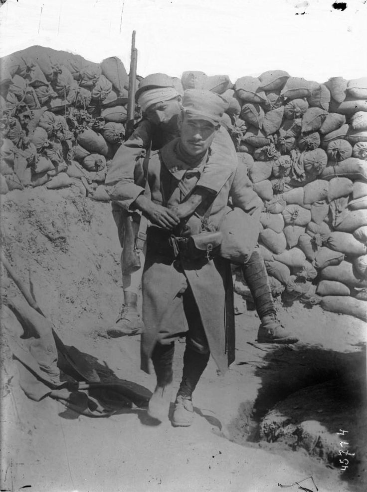 WWI. French soldier carrying a wounded comrade out of the line during the Gallipoli campaign, 1915.