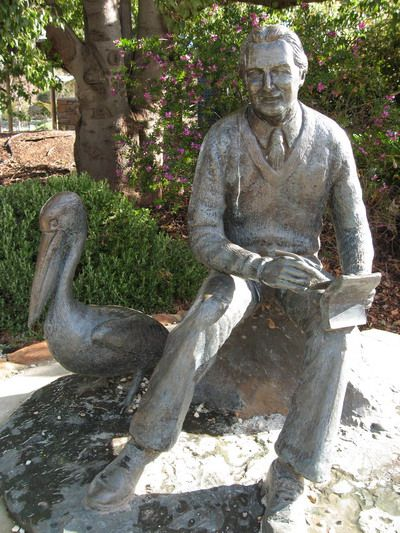 "Memorial to Colin Thiele (1920-2006) author of ""Storm Boy"" sculpted by local artist Christopher Radford F.R.S.A. The statue shows the author with the pelican Mr Percival. It is situated in the Eudunda Town Gardens, Eudunda, South Australia and was unveiled in 1988in its original fibreglass form."