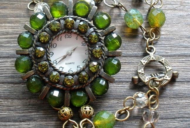 Funkčné hodinky vo vintage ladeni s jemnou zelenkastou patinou.  Hodinky sú vybíjané trblietavými olivovo zelenými zirkónmi a brúsenými kameňmi. Ciferník je doplnený ohňovkami (brúsené sklo) v opálovo-zelenej farbe s travertínovým povrchom (akoby kameninový, zašlí ), béžové brúsené donuty, jasno zelené ohňovky a filigránové starozlaté guličky.  Na starozlatých komponentoch.