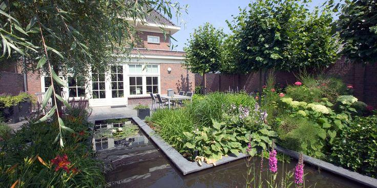 Centraal in deze tuin is de smalle #vijver in het verlengde van de openslaande deuren. Optisch van binnenuit gezien, lijkt het alsof de woning de #vijver naar binnen haalt.