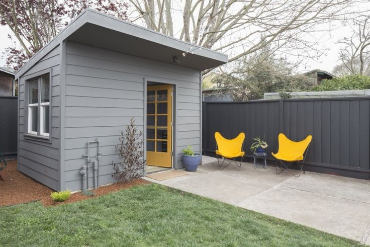 Beautiful modern color co-ordinated timber outdoor garden room with nearby seating