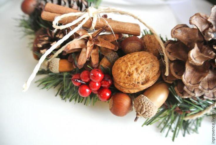Сегодня, как и обещала, после мастер-класса по изготовлению осеннего веночка, мы сделаем с вами новогодний венок из шишек и орехов. Для начала нам понадобится кольцо или из пенопласта (как в моем случае), или из картона. Затем — обматываем кольцо репсовой или атласной лентой, возможно использование любого шнура, джута или даже молярного скотча. На горячий пистолет приклеиваем шишки и искусственные еловые веточки.