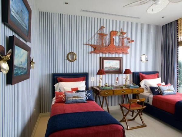 Nautical-inspired boy's bedroom with red and blue accents and striped wallpaper
