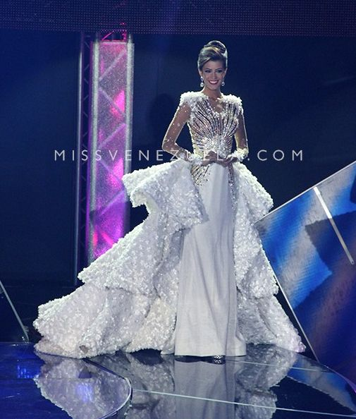 Raymar Lisett Valbuena Cardozo, Miss Zulia 2016, wore this show-stopping white evening gown designed by Nidal Nouaihed when she competed at Miss Venezuela 2016!  The Color  White is definitely a great choice for Raymar. It accents her darker facial features and gorgeous deep brunette hair perfectly while giving her that pop that is so necessary for any contestant to stand out amongst her competition.  This color also helps the gown stand out beautifully against the dark stage backdrop. Here…