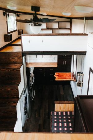 The Ironclad by Wind River Tiny Homes - custom storage stairs, storage couch, shaker style closet, natural pine ceiling, ship lap, cozy cabin propane wall heater