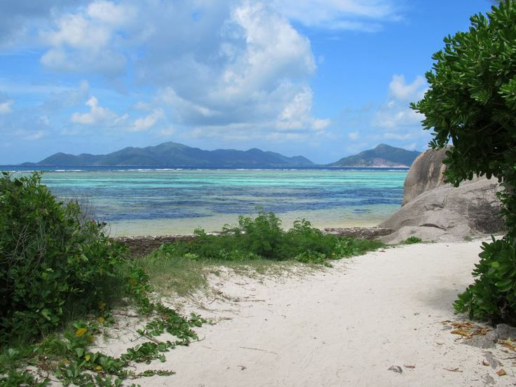 Praslin Island is visible across the strait from Anse Source d'Argent Beach on La Digue Island, Seychelles.