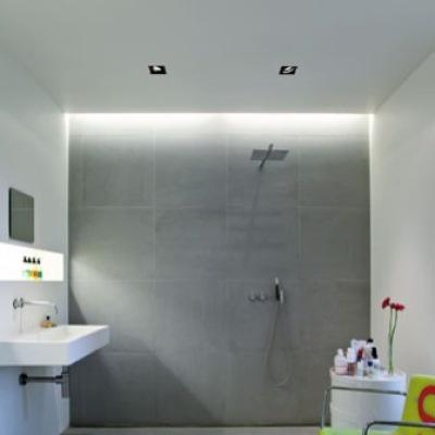 Arkitekt Mette Nygaard har moderniseret familiens badeværelse i Århus i en tidsløs stil med en grå betonlignende væg og hvide omgivelser. Pangfarvet tilbehør giver rummet friskhed.