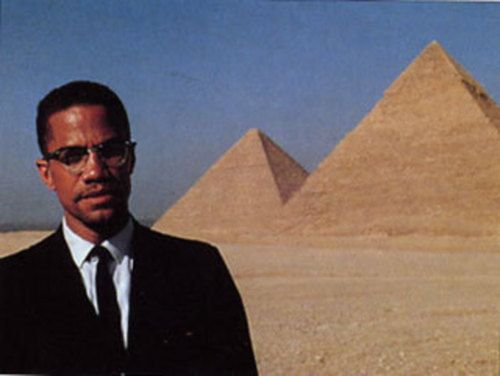 Malcom X standing just outside of The Great Pyramids of Giza, in Egypt