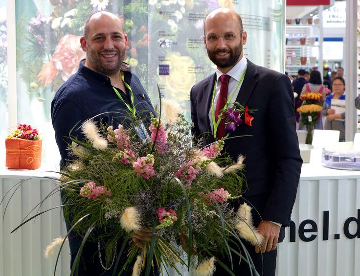 Floristmeister Stefan Prinz und Florian Karner, Vertreter der Deutschen Botschaft, am Deutschen Gemeinschaftsstand auf der HortiflorExpo IPM China 2016 in Peking.