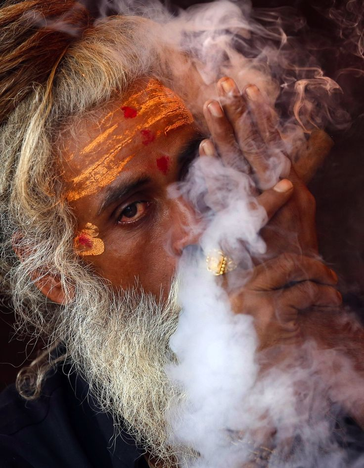 A Naga sadhu, or naked Hindu holy man, smokes hashish inside his tent during Kumbh Mela, or Pitcher festival, at Trimbakeshwar, India.