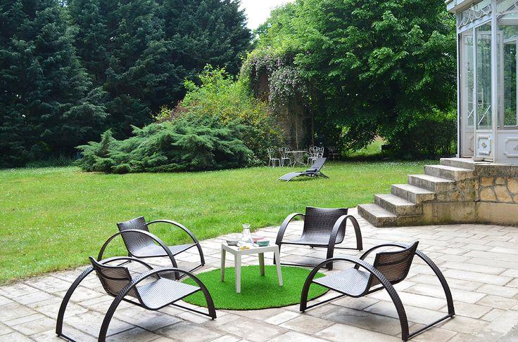 Un jardin et une terrasse avec un tapis en gazon synthétique pour une