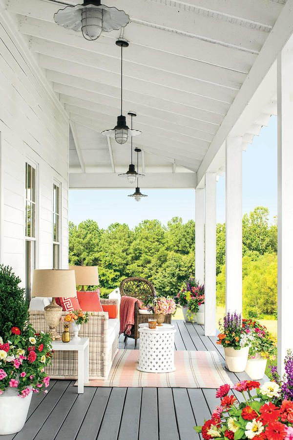 With a few easy and cheerful touches, this porch went from drab to fab. Furnishings with an interior influence like the rug, sofa, and lamps look great in an outdoor room too. Colorful blooming containers in varying sizes create a garden setting.
