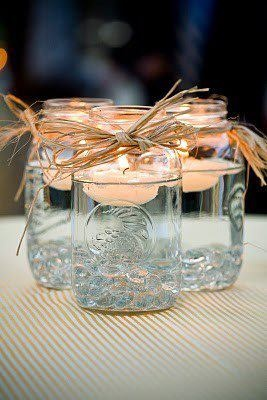 Mason jar with floating candles......I think this would be a good idea outside for a summer dinner or get together.