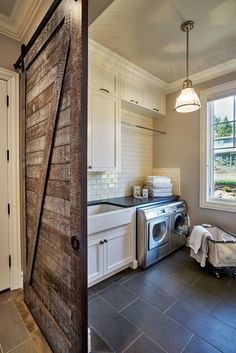 Rustic laundry room featuring a sliding barn door, gray tile floors, stainless steel appliances, white subway tiles and a classic farmhouse sink   Garrison Hullinger