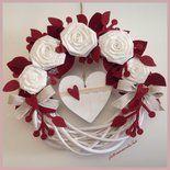 Corona di legno bianca decorata con 5 rose di lino bianco, rametti e foglie di feltro e panno bordò, nastro di lino e cuoricini di feltro. All'interno un cuore di legno bianco ornato con pizzo e cu...