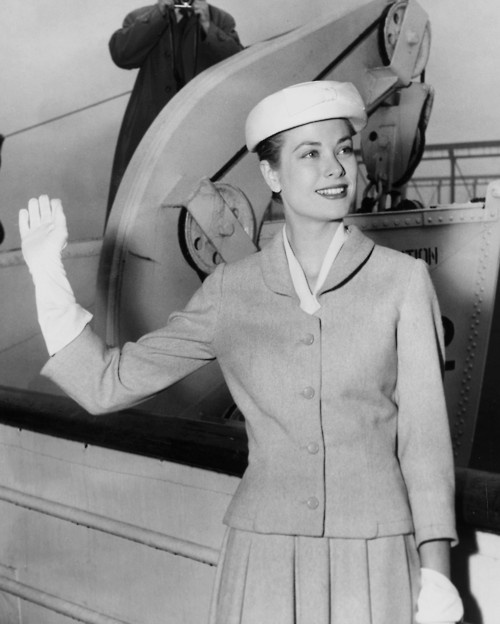 Grace Kelly waves good bye to New York from the deck of the liner SS Constitution, before sailing for Monaco and her wedding to Prince Rainier. The lone cameraman getting another angle on the departure is United Press Staff Photographer Joe Schuppe, who is accompanying the actress on the crossing to provide picture coverage aboard and at the wedding for United Press clients. April 4, 1956.