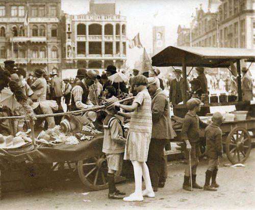Vorstenhuizen : Koningshuis Nederland : Tijdens de Koninginnedagviering in Amsterdam staan mensen te kijken bij diverse kraampjes op de Dam. Op de voorgrond een paar kinderen. Nederland, 1926.