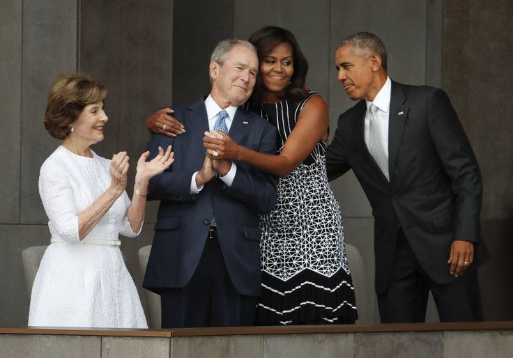 First lady Michelle Obama, center, hugs former President George W. Bush, as President Barack Obama and former first lady Laura Bush walk on stage at the dedication ceremony of the Smithsonian Museum of African American History and Culture at the National Mall in Washington on Sept. 24, 2016.