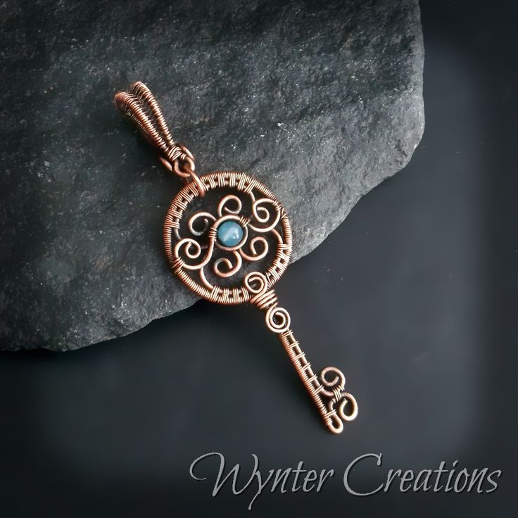 Triphine's Key features intricate copper wire work, accented with a single aqua…