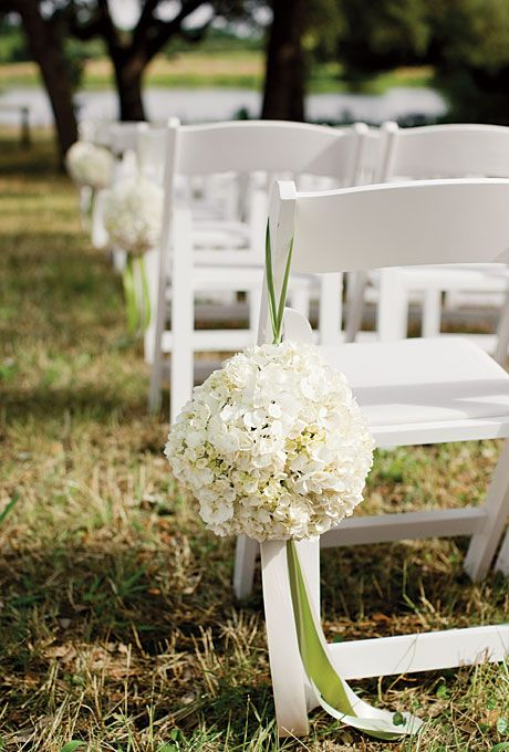 Pomanders of hydrangeas adorned chairs. Photo by Harrison Studio.