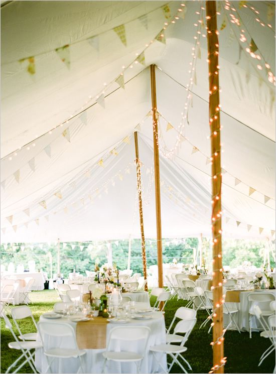Pair bunting with lights to enhance the look of the tent for a backyard wedding.