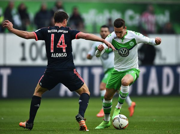 Julian Draxler of Wolfsburg is challenged by Xabi Alonso of Muenchen during the Bundesliga match between VfL Wolfsburg and FC Bayern Muenchen at Volkswagen Arena on February 27, 2016 in Wolfsburg, Germany.