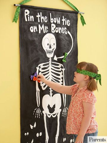 This take on the classic party game uses a skeleton and bows rather than a donkey and tails for a Halloween twist. To make it, download the template and enlarge as desired. Tape the pattern to a window or glass door, cover it with the canvas, and transfer the pattern onto the canvas with a pencil. Paint the skeleton and background, referring to the photo for color placement; let dry. Sew a rod pocket across the top to accommodate a dowel. Paint the dowel with black and white acrylic paint…