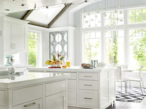 In a Rye, New York, kitchen designed by Louise Brooks, custom cabinetry in Benjamin Moore's high-gloss Super White is topped with counters made of crystallized glass by Glassos. The Glassos countertop has the gleam of Thassos marble, but with zero porosity. Chandelier by Bocci.   - HouseBeautiful.com