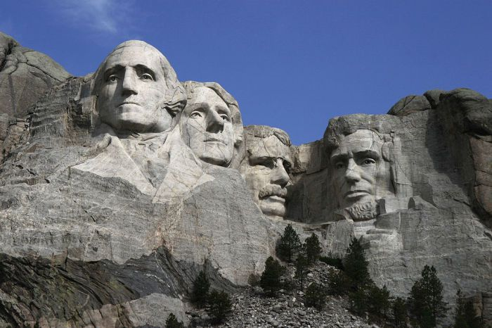 На фотографии запечатлён момент создания барельефа на горе Рашмор. Это 1941 год. До завершения проекта ещё несколько лет. Барельеф высотой 18,6 метров, на котором запечатлены портреты четырёх американских президентов, - Джорджа Вашингтона, Томаса Джефферсона, Теодора Рузвельта и Авраама Линкольна – создавали на протяжении 14 лет. Одновременно на площадках, закреплённых на высоте стальными тросами, работало до 30 человек.