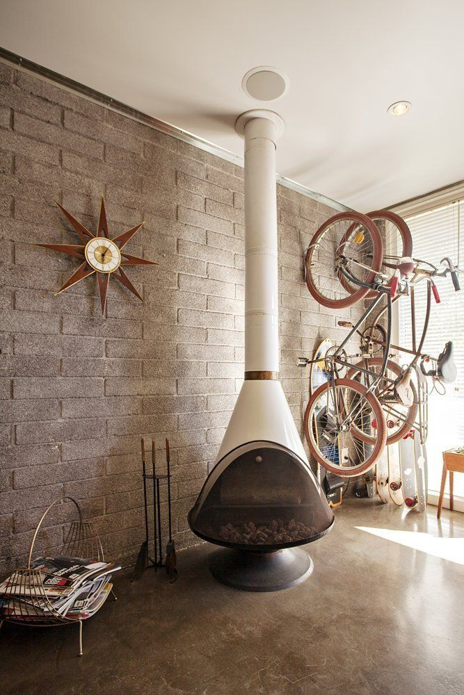 malm fireplace in a midcentury living room with concrete floors and bike storage