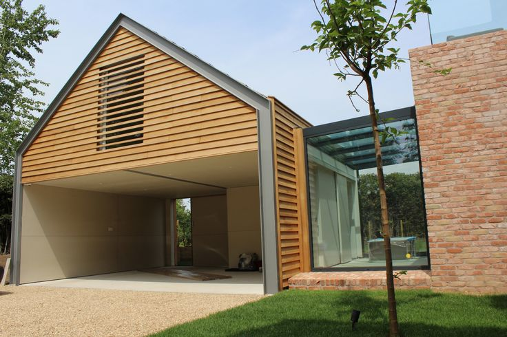 Contemporary cedar clad car barn with louvres and steel portal frame feature. A glass link connects the garage to a new brick extension, creating a courtyard.