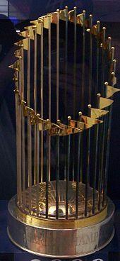 A golden circular shaped trophy on a red platform.