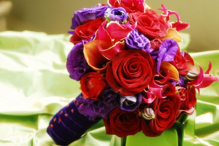 Unique red and purple boquet with red roses, orange calla lilies, gloriosa, and purple lisianthus.    www.helenolivia.com