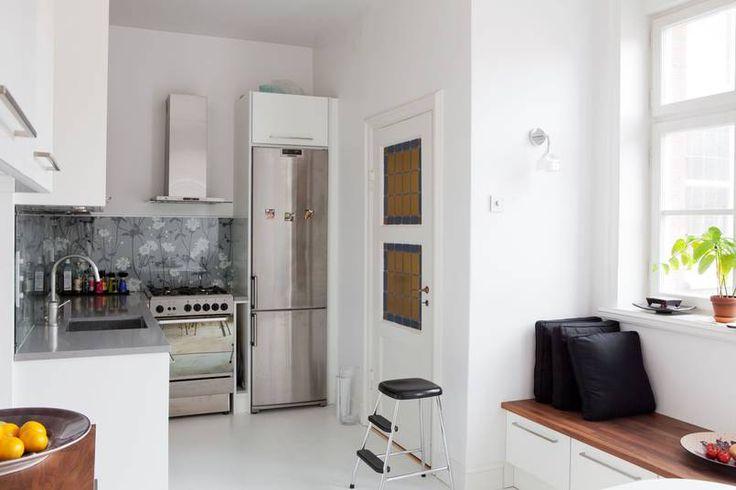 Stalowe sprzęty, szary kamienny blat i białe meble tworzą w tej kuchni nowoczesny chłodny wystrój. By go wizualnie ocieplić, za szklanym panelem chroniącym ścianę przy kuchence i zlewie przyklejono tapetę. Choć jest utrzymana w gamie szarości, kwiatowy wzór robi przyjazne wrażenie.