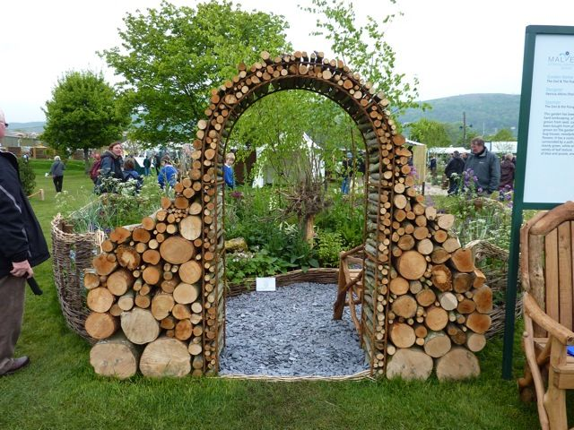 Garden arch made of short logs. Drill them and it's a big bug hotel!