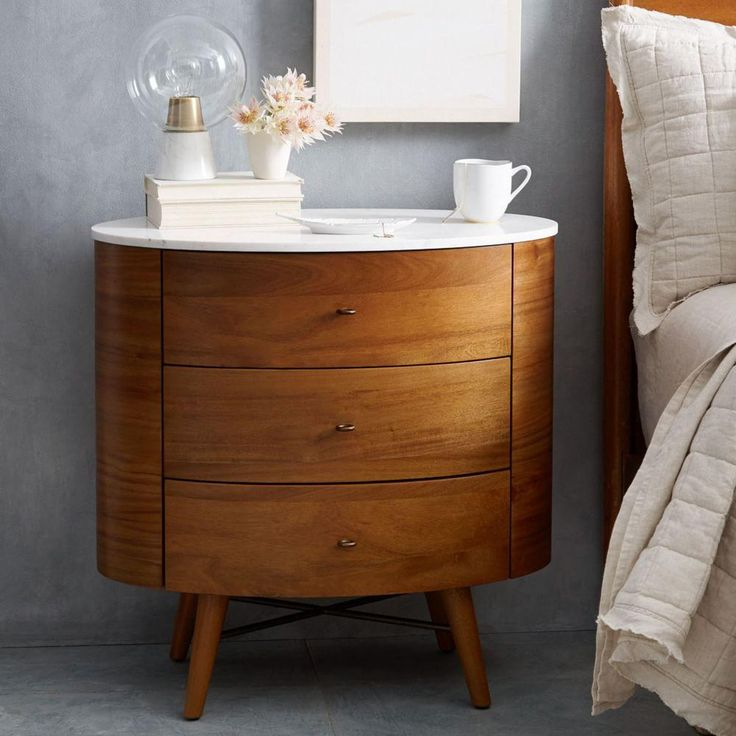 Our Penelope Bedside Table's slim, tapered legs and refined profile are inspired by mid-century design. Its marble top is wide enough for stacks of bedtime reading, while three rounded drawers provide plenty of storage for knickknacks.