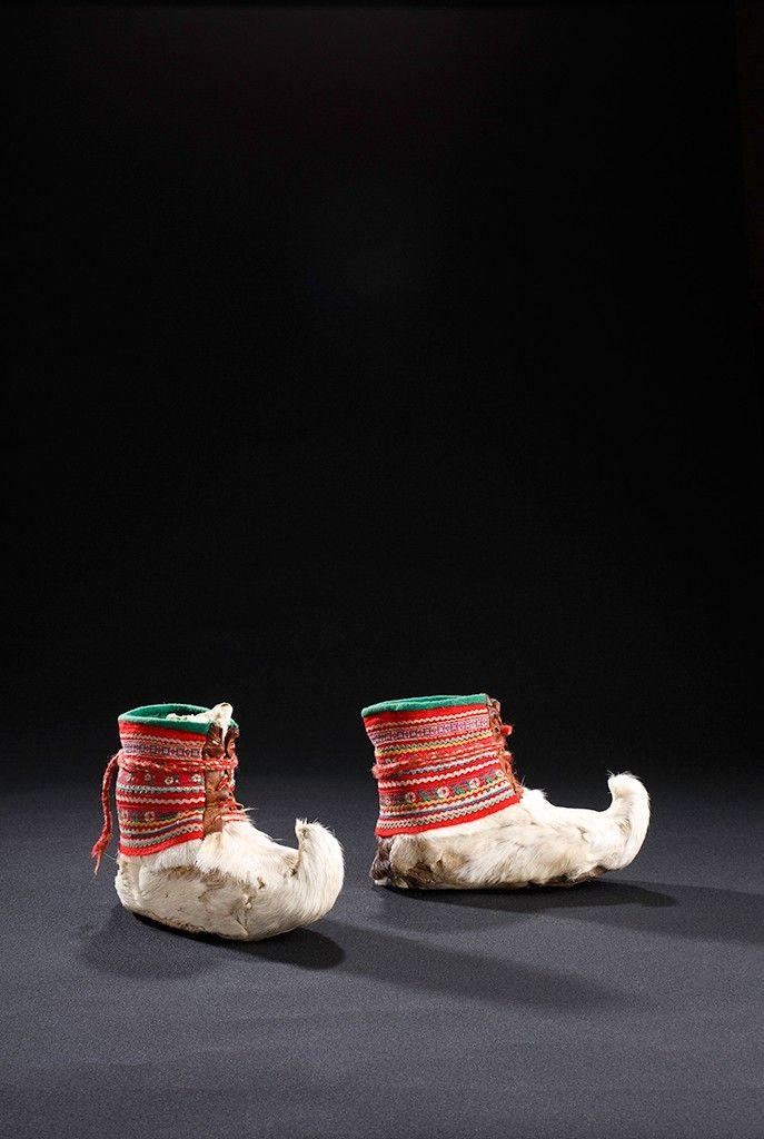 Saami levantou os sapatos de dedo do pé  Saami. Aiddejavre, Noruega  Botas em Sápmi compartilhar uma série de características comuns, a partir do uso de têxteis coloridos para o dedo do pé distintivo virado para cima. No entanto, as diferenças regionais também estão presentes. As diferentes cores e padrões encontrados nos laços longos, chamados vuoddagat, refletem diferenças regionais. Os detalhes da construção também revelam onde as botas foram feitas. Fotografia: Ron Wood.