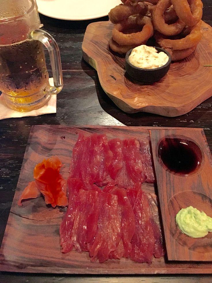 Delish combo of Bintang beer, fried onion rings and sashimi