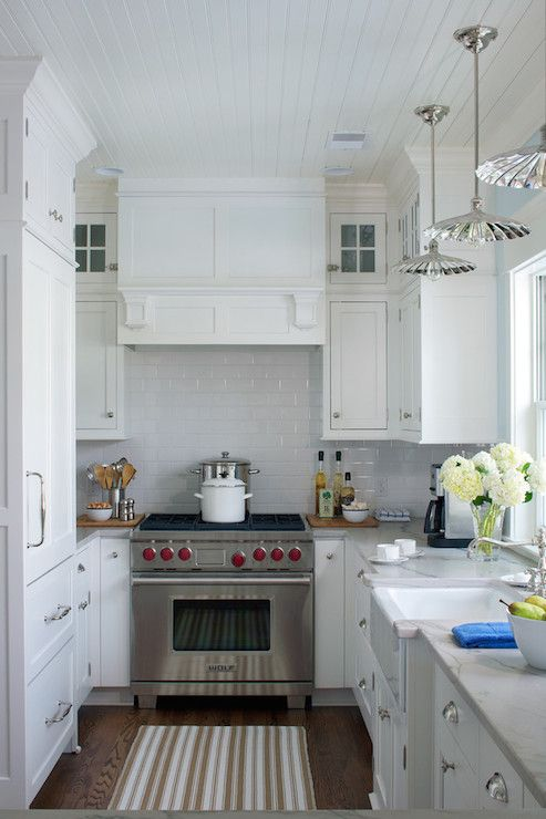 {Signature Kitchens Online} Cottage style kitchen with beadboard ceiling over double stacked upper cabinetry accented with nickel pulls and marble counters with a classic subway tiled backsplash. The narrow U-shaped kitchen features a cabinet front refrigerator with dual freezer drawers opposite the apron kitchen sink illuminated by Heirloom Pendants by Hudson Valley Lighting, with a stainless steel stove with paneled range hood at the far end of the space.