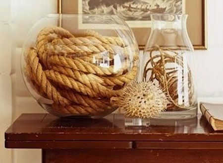 Nautical rope centerpiece in fishbowl with milk jug accented piece    I love this idea of a vignette for an entry table. Calaixera tamariu, mes safata pell amb llibres i per sobre coral blau.