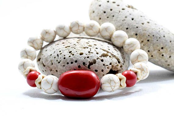 Womens Beaded Bracelet, features 10mm White Howlite Gemstone beads with two 9mm and one large Red Coral root bead. A handsome piece of womens jewelry which attracts the eye! Wear alone or stack with other AlterDeco bracelets for another stylish option. ► Your bracelet comes with a beautiful pouch, ready to be offered as a gift!  Details: 10mm White Howlite Gemstone beads Two 0.35 / 9mm Red Coral root beads One Large 0.91 X 0.55 / 23 X 14 mm Red Coral root bead Quality Transparent St...