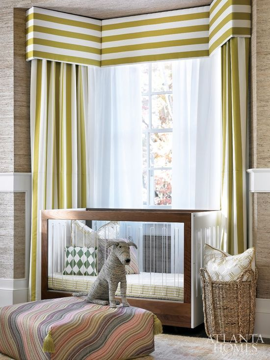 Contemporary nursery features walls clad in mushroom textured wallpaper finished with a thick white chair rail alongside a two tone crib billing a bay window dressed in white and chartreuse striped cornice boxes and white and chartreuse striped curtains.