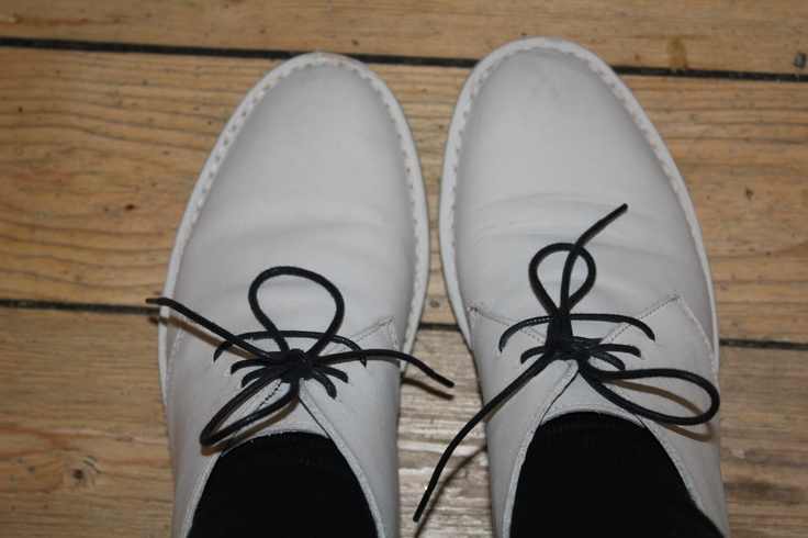 White soft leather shoes. Dark brown shoe laces. Nicely tied. On a pine floor.