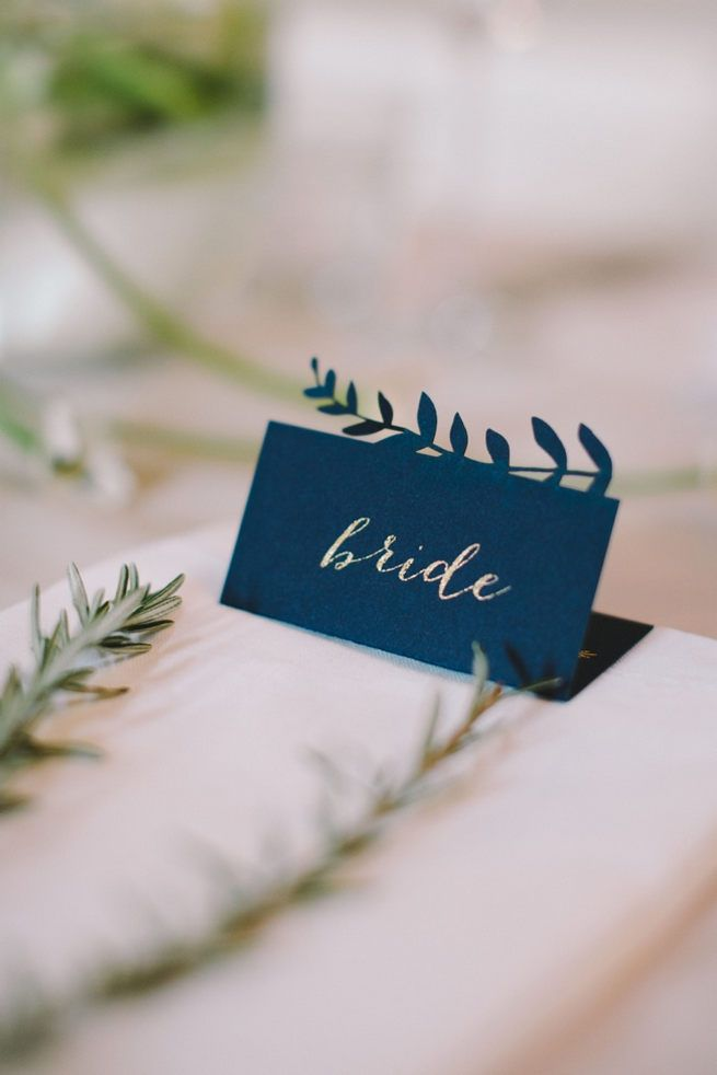 Navy blue bride and groom place cards with leaf patterning.