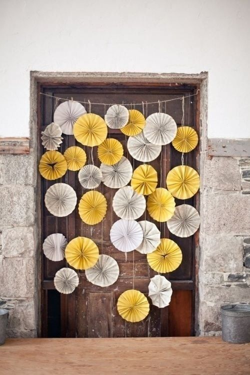 Yellow and white pinwheels hanging on a vintage/rustic door. Great example of working with what's already there.