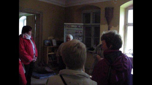 Folk art House Kurava in Latvia:Juustola Craft Association's President Hanna dressed in a traditional costume